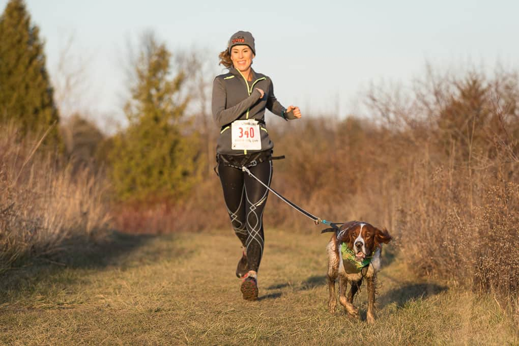 woman runner and her muddy dog at canicross trail race